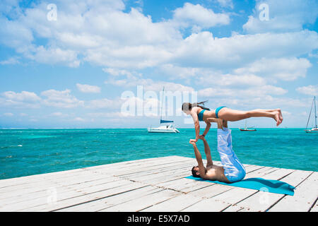 Young couple in airplane pose on pier, San Pedro, Belize - Stock Photo