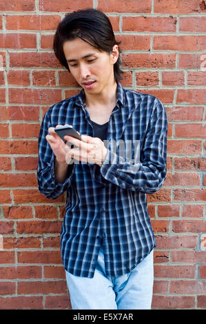 Mid adult man leaning against wall texting on smartphone - Stock Photo