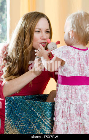Mid adult mother holding up soft toy for baby daughter - Stock Photo