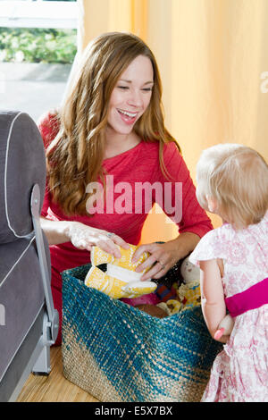 Mid adult mother squeezing soft toy for baby daughter - Stock Photo