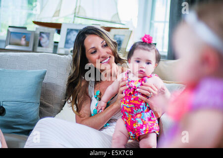Young mother with baby girl in sitting room - Stock Photo