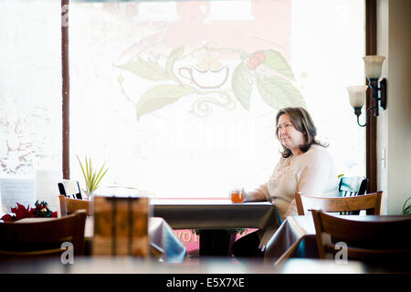 Mature woman having a herbal tea in cafe window seat - Stockfoto