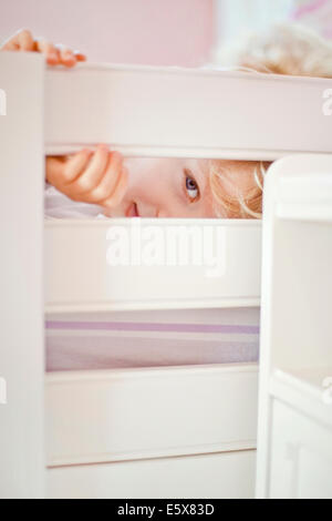 Close up portrait of four year old boy peeking through bed frame - Stock Photo
