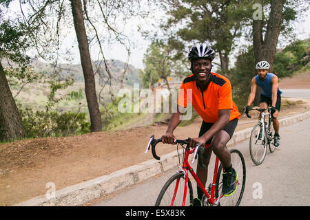 Cyclists on uphill road - Stock Photo