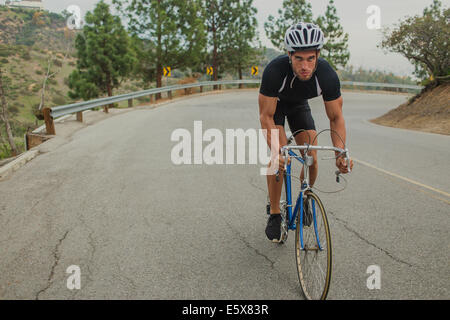 Cyclist on uphill road - Stockfoto