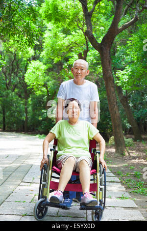 senior woman sitting on a wheelchair with his husband - Stock Photo