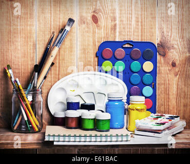 Paintbrushes, watercolor, gouache and paper are on wooden shelf - Stock Photo