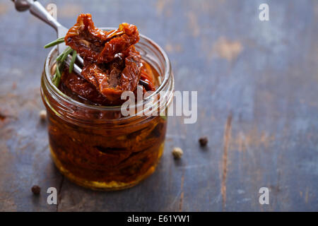 Sun-dried tomatoes in jar on wooden background - Stock Photo