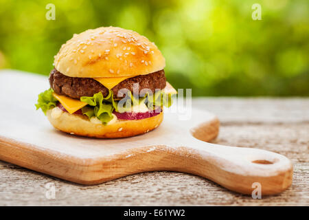Tasty burger with cheese, lettuce, onion and tomatoes served outdoor on a wooden table - Stock Photo