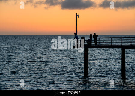 Fishermen on the pier are silhouetted against the sunset at Adelaide's Brighton beach, Australia - Stock Photo