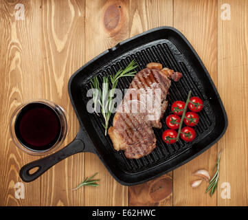 Sirloin steak with rosemary and cherry tomatoes on frying pan with glass of wine - Stock Photo
