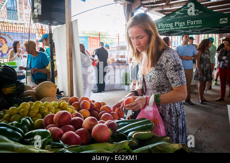 Customer buys produce at the Youthmarket stand during the re-opening of La Marqueta in the East Harlem neighborhood - Stock Photo