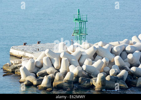 Man standing beside Dolosse precast concrete blocks in breakwater to protect  green channel marker on the harbour - Stock Photo