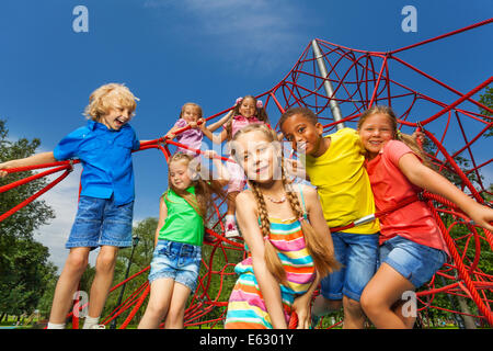 Many kids stand on red ropes together in park - Stock Photo