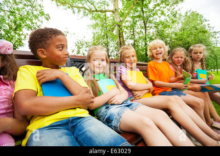 Happy school kids on bench sit in row together - Stock Photo