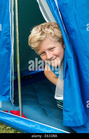 A boy, 10 years, looking out of his tent - Stock Photo
