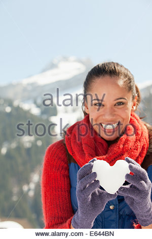 Portrait of smiling woman holding heart-shape snowball - Stock Photo