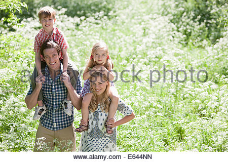 Parents holding children on shoulders in park - Stock Photo