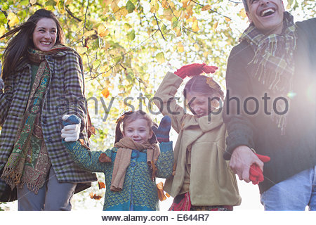 Family laughing and holding hands outdoors - Stock Photo