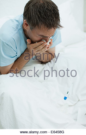 Sick man in bed blowing nose - Stock Photo