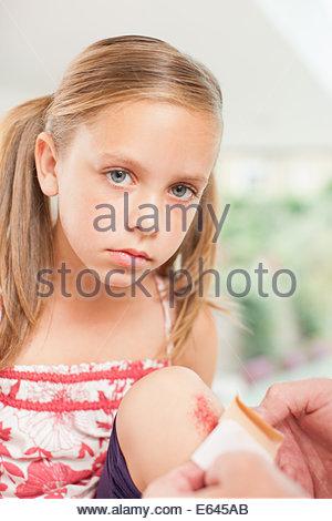 Close up of putting bandage on girl knee - Stock Photo