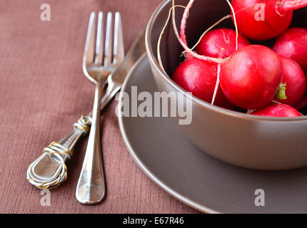 Few fresh radishes in a ceramic bowl with fork and knife on a table - Stock Photo