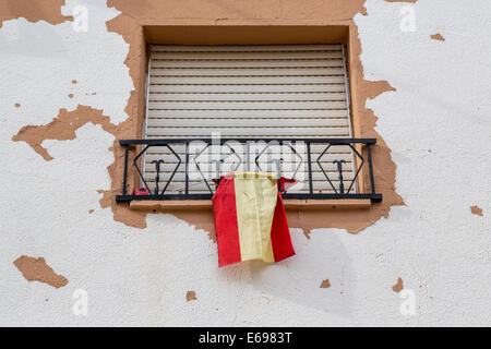 Window with closed blinds and Spanish flag, Humanes, Province of Guadalajara, Spain - Stock Photo