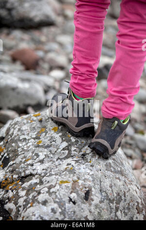 Child wearing walking boots and standing on a lichen-covered rock on a coastal path in Scotland. - Stock Photo