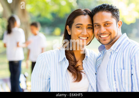 happy Indian couple standing in front of children outdoors - Stock Photo
