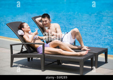 Young couple sunbathing at the poolside - Stock Photo