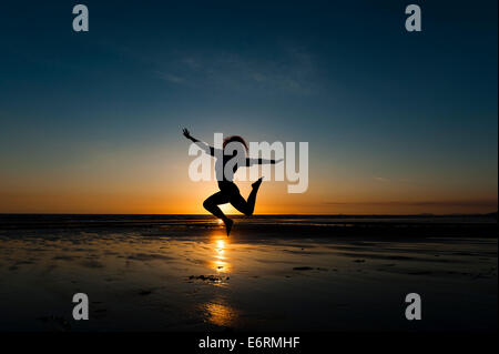 Summer evening: A young woman girl leaping in silhouette at sunset, Ynyslas Beach, Cardigan Bay, west wales UK - Stock Photo