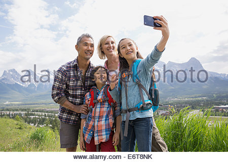 Family taking cell phone picture on rural hillside - Stockfoto