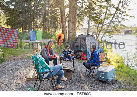 Family relaxing together around campfire - Stock Photo