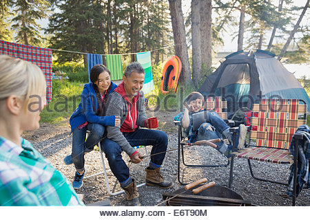 Family relaxing together around campfire - Stockfoto