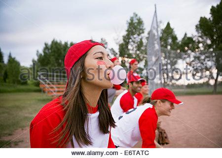 Baseball player blowing bubble gum bubble on field - Stock Photo