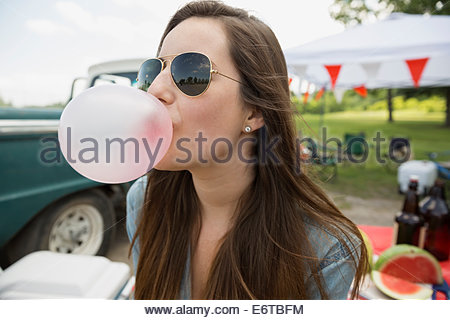 Woman blowing bubble gum bubble at tailgate barbecue - Stock Photo