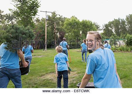 Portrait of smiling volunteer pushing wheelbarrow - Stock Photo