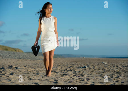 A young ethnic asian chinese  woman girl wearing a white dress holding her shoes walking alone along a sandy beach - Stock Photo