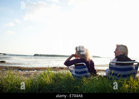 Mother and daughter enjoying view on beach - Stock Photo