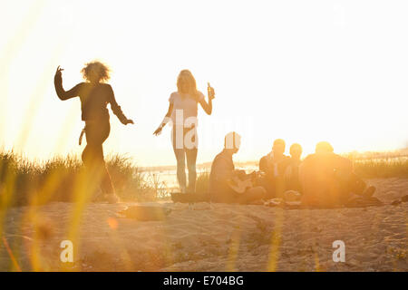 Six adult friends partying at sunset on Bournemouth beach, Dorset, UK - Stock Photo