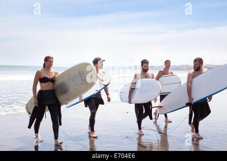 Group of male and female surfer friends walking away from sea with surf boards - Stock Photo