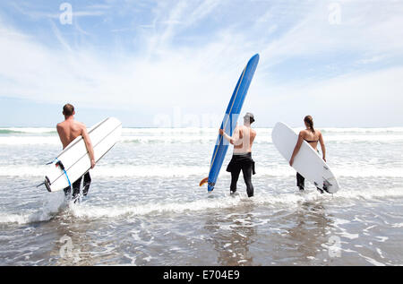 Male and female surfer friends standing in sea with surf boards - Stock Photo