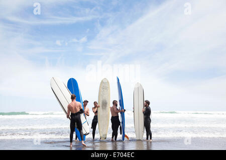 Group of male and female surfer friends standing on beach with surf boards - Stock Photo