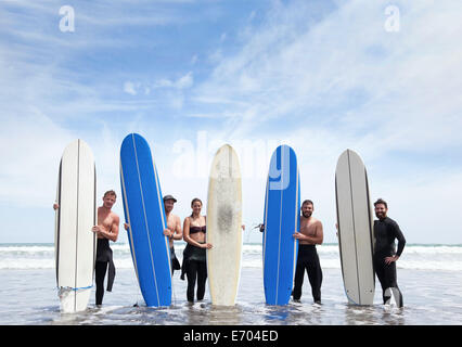 Group portrait of male and female surfer friends standing in sea with surfboards - Stock Photo