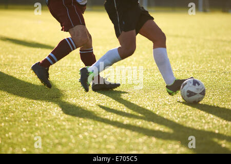 Footy players fighting for ball - Stock Photo