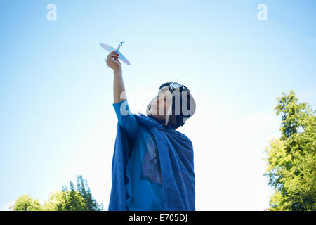 Young boy in fancy dress, playing with toy aeroplane - Stock Photo