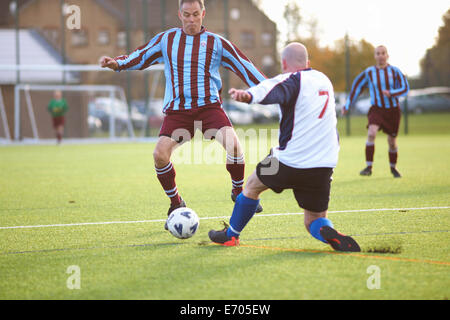 Football players fighting for ball - Stock Photo