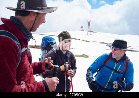 Three hikers in snow, Bucegi Mountains, Transylvania, Romania - Stock Photo