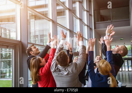 Group of businesswomen and men raising hands together in a circle - Stock Photo