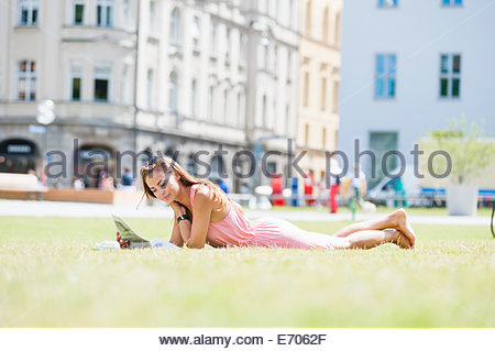 Mid adult woman lying on grass, reading newspaper - Stock Photo